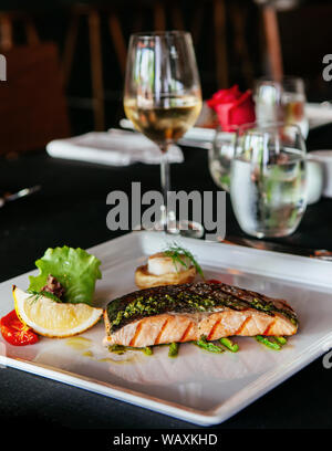 Beautiful delicious salmon steak with grilled asparagus and pesto sauce, fine dinning cuisine - Stock Photo