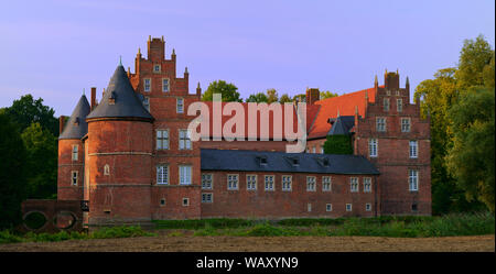 Beautiful Herten castle, illuminated by the evening sun in August. Moated castle in North Rhine Westphalia, Germany. - Stock Photo