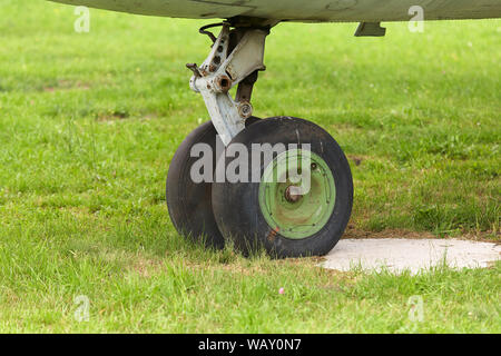Old chassis of an old airplane close up on a background of green grass.