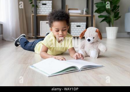 Adorable preschooler mixed race child boy reading book at home - Stock Photo