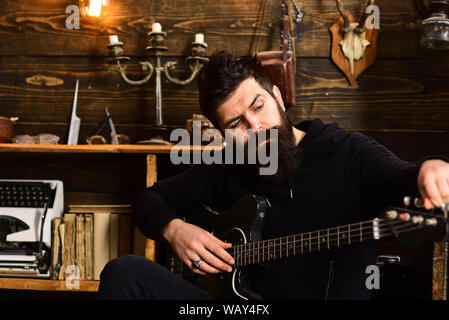Guitar as hobby. Guy in cozy warm atmosphere play favourite music. Man with beard holds black electric guitar. Man bearded musician enjoy evening with - Stock Photo