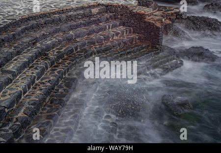 stone steps in the Atlantic Ocean, long exposure photography, with evening light, La Caleta, El Hierro, Canary islands, Spain - Stock Photo