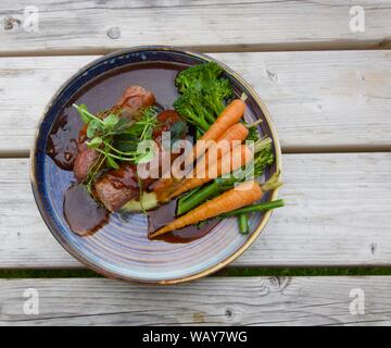 Delicious meal of sausages and fresh carrots on plate - Stock Photo
