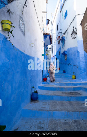 Lady walking down the street in Chefchaouen - Stock Photo
