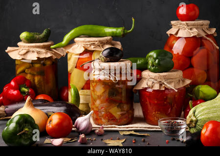 Different pickled vegetables in glass jars for long-term storage: salad with eggplant, peppers, cucumbers, tomatoes and mixed vegetables against a - Stock Photo