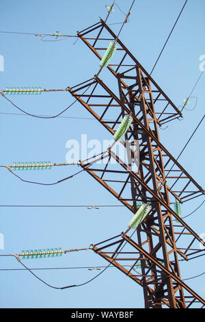 Bottom view on high voltage power lines against blue cloudless sky