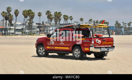 LOS ANGELES, CA / USA - MAY 23, 2017: A lifeguard patrolling in a vivid red Toyota Tacoma special off road pick up truck on Venice Beach, - Stock Photo