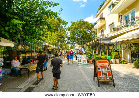 Tourists walk the crowded path past cafes, street vendors and souvenir shops in the Monastiraki district of Athens, Greece on a summer day - Stock Photo