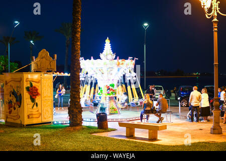 A small, colorful carousel is a spinning blur as parents and local Italians enjoy a night out on the Piazza Vittorio Emanuele II in Brindisi Italy - Stock Photo