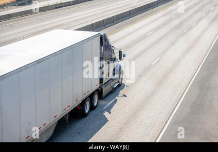 Big rig dark powerful professional American bonnet industrial grade semi truck transporting commercial cargo in dry van semi trailer running on the wi - Stock Photo