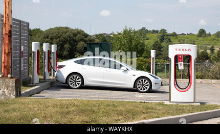 Tesla Model 3 parked and charging at Tesla Supercharger Station. - Stock Photo