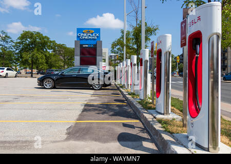Tesla Model 3 parked and charging at Tesla Supercharger Station on sunny day. - Stock Photo