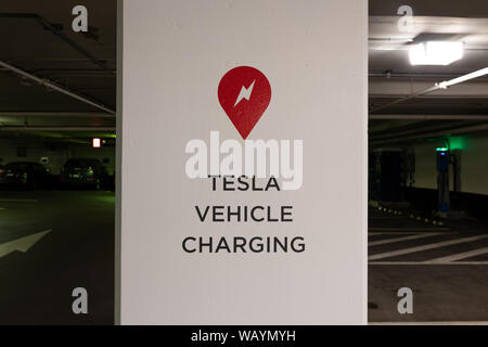 Tesla Supercharger logo and Tesla Vehicle Charging text on post in parking garage in-front of Tesla Supercharger Station. - Stock Photo
