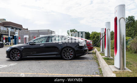 Black Tesla Model S plugged-in and charging at Tesla Supercharger Station with other vehicles charging behind. - Stock Photo