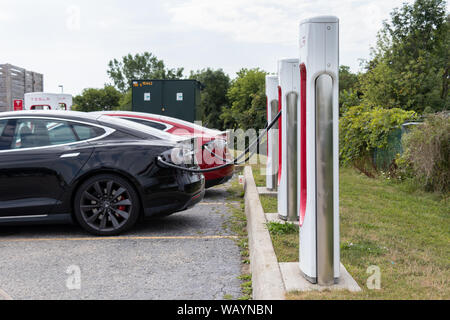 Two Tesla Model S's parked and charging at Tesla Supercharger Station. - Stock Photo