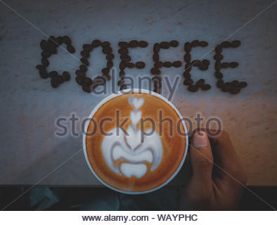 white ceramic cup filled with coffee and cream close-up photography - Stock Photo