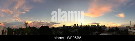 A panoramic shot of manila city buildings under a light blue sky at sunset - Stock Photo
