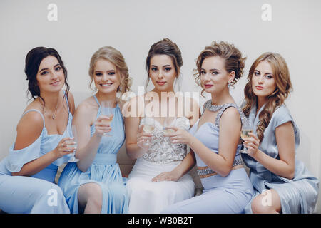 elegant and stylish bride along with her four girlfriends in blue dresses sitting in a room - Stock Photo