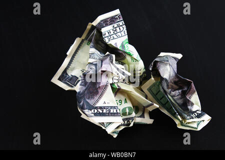 Crumpled one hundred American dollar on black paper background, close-up of bad money. The collapse of the dollar. Devaluation. Falling currency. - Stock Photo