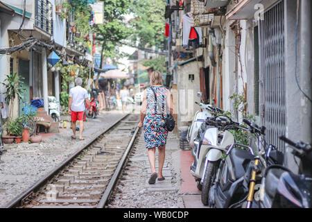 A woman is walking on the railway in Train street, Hanoi, Vietnam