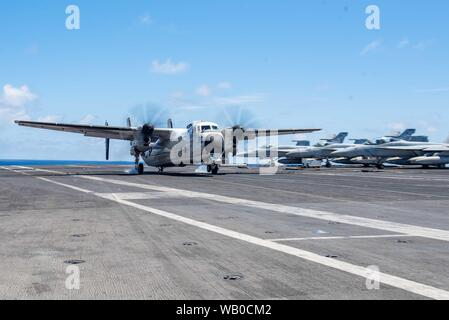 190822-N-CL027-1210 EAST CHINA SEA (August 22, 2019) A C-2A Greyhound from Fleet Logistics Support Squadron (VRC) 30 lands on the flight deck aboard the Navy's forward-deployed aircraft carrier USS Ronald Reagan (CVN 76) during flight operations. Ronald Reagan, the flagship of Carrier Strike Group 5, provides a combat-ready force that protects and defends the collective maritime interests of its allies and partners in the Indo-Pacific region. (U.S. Navy photo by Mass Communication Specialist 2nd Class Janweb B. Lagazo) - Stock Photo