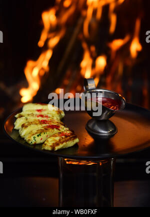 Freshly cooked cranberry dipping sauce in saucepan. Dipping sauce served to food items on burning flame background. Food at first sight - Stock Photo