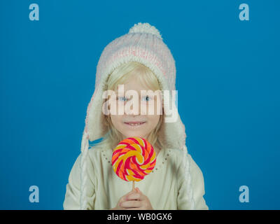 A sweet tooth. Little girl hold lollipop on stick. Little child with sweet lollipop. Happy candy girl. Happy childhood food - Stock Photo