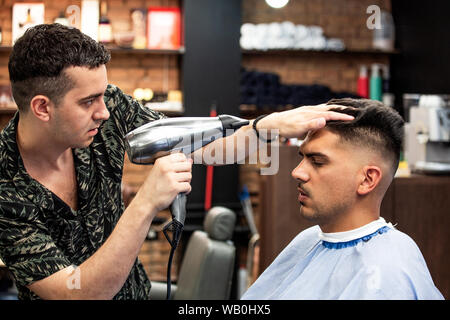 Close-up, master Barber does the hairstyle and styling with dryer, dries hair to guy. Concept Barbershop. Soft focus. - Stock Photo