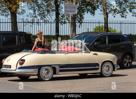 Saint Emilion, France - September 8, 2018: Tourists in an old beautifully preserved convertible in Saint Emilion. France.  St Emilion is one of the pr - Stock Photo
