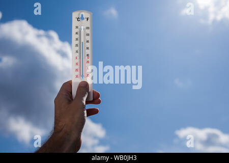 Man keep thermometer in hand at sky with clouds background. Weather concept - Stock Photo