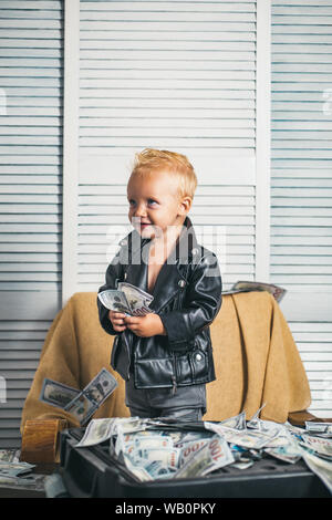 Hes rolling in money. Boy child with money case. Little boy count money in cash. Small child do business accounting in startup company. Little entrepr - Stock Photo