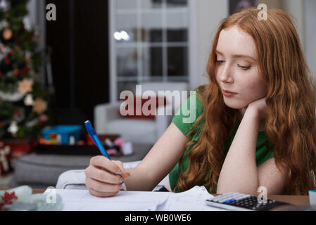 Teenage girl (13-15 years) doing homework - Stock Photo