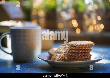 Teacup and Christmas gluten free cookies on a table near the window - Stock Photo