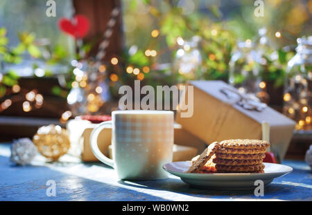Teacup and Christmas gluten free cookies on a table near the decorated window with gift boxes - Stock Photo
