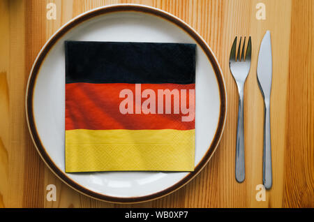 Plate and serviette with a German flag pattern lying on a wooden table. Fork and knife, cutlery. German cuisine concept. Food in Germany. Traditional dish, meal. Bavaria, Oktoberfest. - Stock Photo