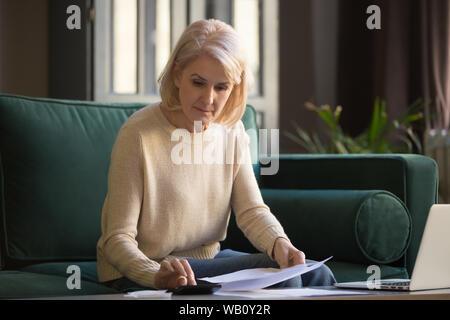 Serious mature woman holding bills doing paperwork using calculator - Stock Photo