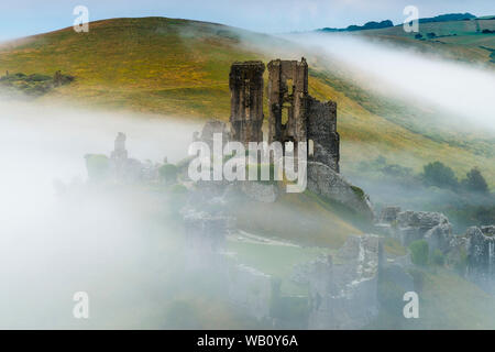 Corfe Castle, Dorset, UK.  23rd August 2019.  UK Weather.  A moody start to the day as the mist begins to break up shortly after sunrise at Corfe Castle in Dorset.  The weather is forecast to be hot and sunny this Bank Holiday weekend.  Picture Credit: Graham Hunt/Alamy Live News - Stock Photo