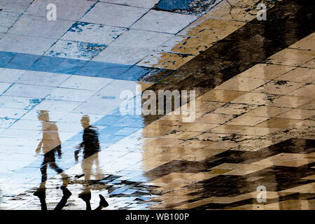 Blurry reflection shadow silhouettes of  two young men walking on a vintage pavement on wet city street, one carrying a bottle and a sac - Stock Photo