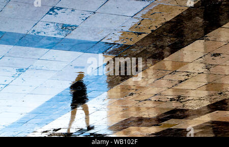 Blurry reflection shadow silhouettes of  one person  walking on a vintage pavement on wet city street - Stock Photo
