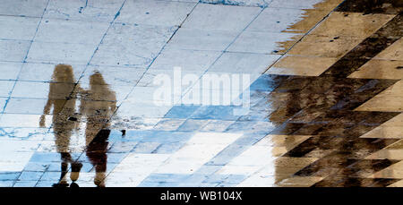 Blurry reflection shadow silhouettes of  two girl friends walking on a vintage pavement on wet city street - Stock Photo