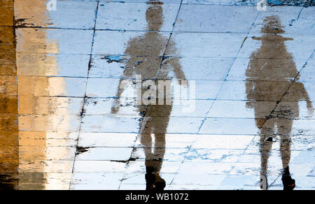Blurry reflection shadow silhouettes of two people walking on a wet street  on a summer day in the city - Stock Photo