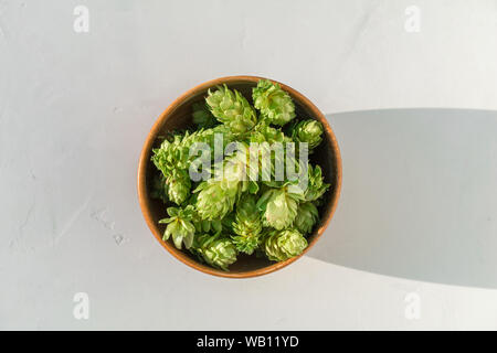 Hops in wooden bowl on grey concrete background. Close up of fresh seed cones from the hop plant, Humulus lupulus. Top view - Stock Photo