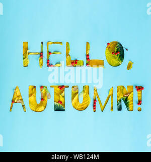 Hello Autumn voluminous text from yellow autumn leaves and orange rowan berries on a blue background. Seasonal lettering - Stock Photo