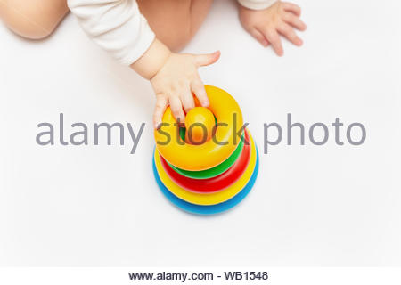 Baby boy playing with colorful rainbow toy pyramid. Child Sorting Objects. Toys for little kids. Child with educational toy. Infant early development. - Stock Photo