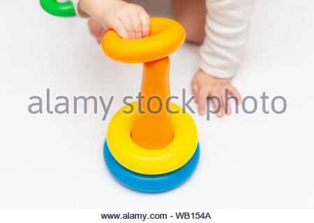 Baby playing with colorful rainbow toy pyramid. Child Sorting Objects. Toys for little kids. Infant early development. - Stock Photo