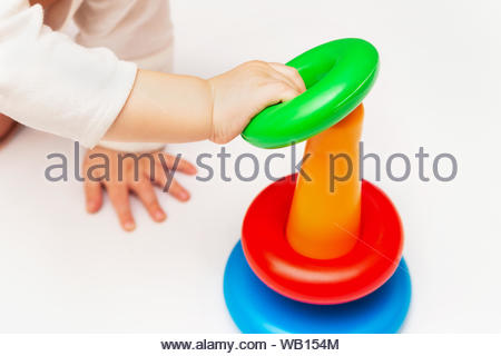 Baby playing with colorful rainbow toy pyramid. Child Sorting Objects. Toys for little kids. Child with educational toy. Infant early development. - Stock Photo