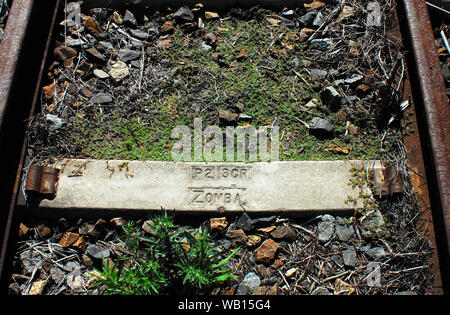This old rusted railroad tie near Knysna, South Africa has the word ZOMBA stamped on it.  Some books indicate it may refer to Zomba, in Malawi. - Stock Photo