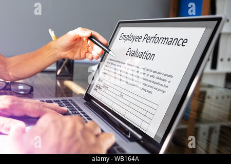 Close-up Of Two Businesspeople Filling Employee Performance Evaluation Form On Laptop Over Office Desk - Stock Photo