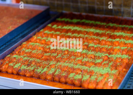 Kunafa Rolls. Turkish dessert kunefe, knafeh, kunafa, kadayif with pistachio powder and cheese hot eaten a sweet. - Stock Photo