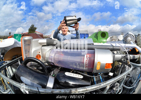 man leaving electrical appliance (weee) for recycling at council household recycling centre united kingdom - Stock Photo